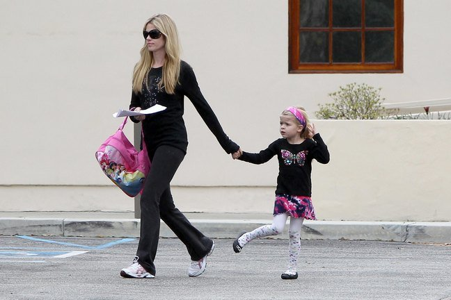 Denise Richards black long sleeved shirt yoga pants carrying backpack