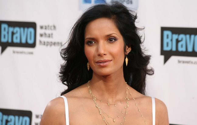 Padma Lakshmi white spaghetti strap dress, gold earrings, gold layered necklace
