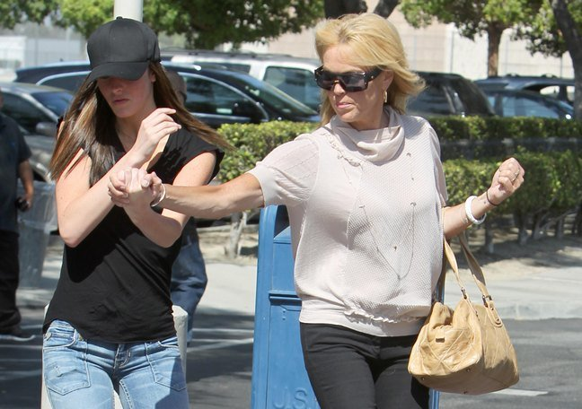 Dina Lohan, White blouse, tan bag, necklace, sunglasses, black pants, bracelets