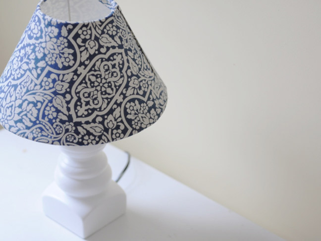 A white lamp and lampshade thats been refitted with blue paisley print