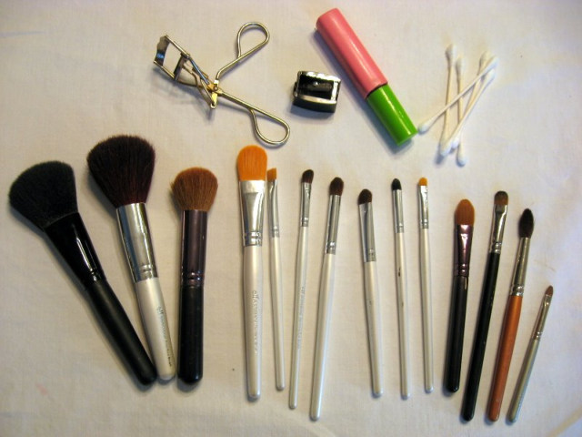 makeup brushes, a eyelash curler and mascara splayed on a table