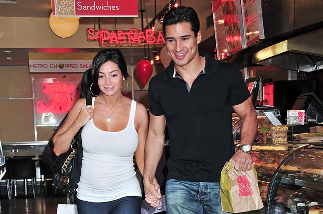 Mario Lopez, black polo, jeans, watch, Courtney Mazza, white tank top, hoop earrings, black tote, black bag, leggings, necklace