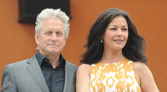 Michael Douglas, gray suit jacket, black dress shirt, Catherine Zeta-Jones, orange and white print dress, earrings