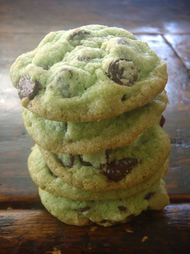 A stack of five chocolate chip cookies with a subtle green tint