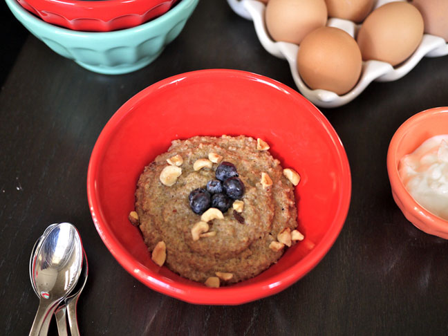coconut almond breakfast quinoa in a red porcelain bowl with blueberries and nuts
