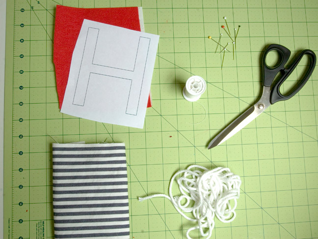 "the letter ""H"" drawn on a piece of paper on top of red felt, pictured with cutting scissors, clothing pins and a cutting board"