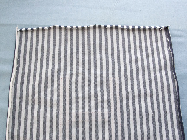 A piece of the blue and white pinstriped fabric is laying face down