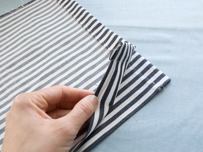 the fabric is folded over in half with one end being held up 8657a3bf59654