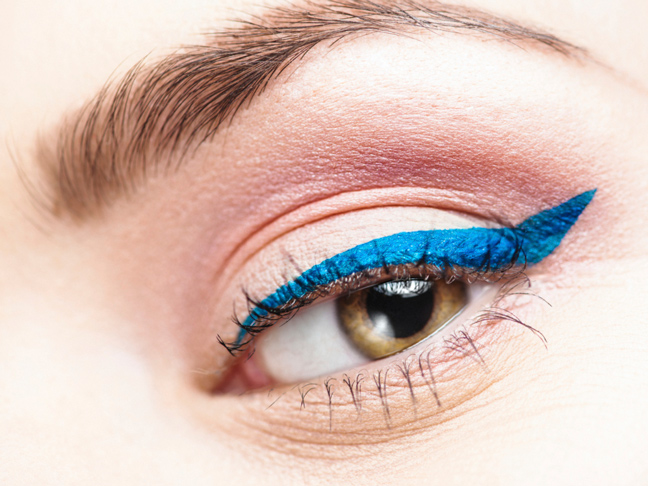 a close up of an eye with matte electric blue winged liner