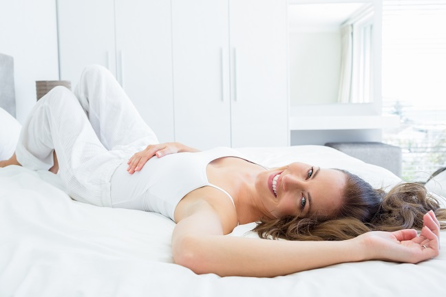 Smiling woman pictured laying in bed