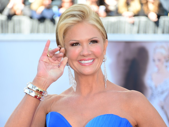 Nancy O'Dell in a blue strapless dress waving at a awards show