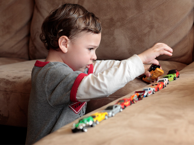 little boy with autism lines up toy cars
