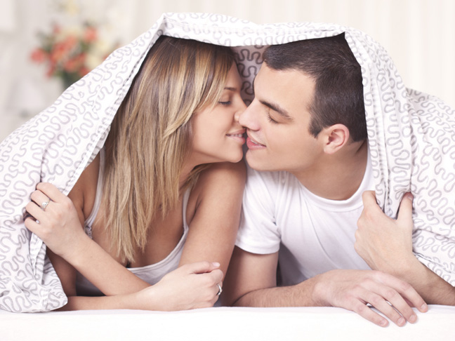 couple pictured in bed kissing