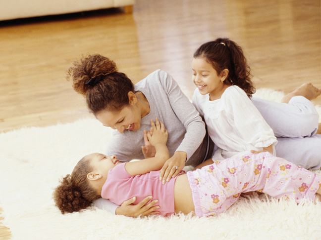 mother playing with kids on the floor