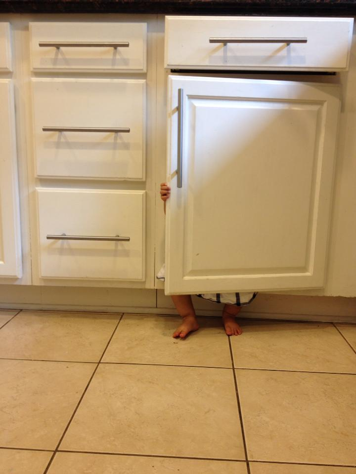 Little girl hiding behind a cabinet