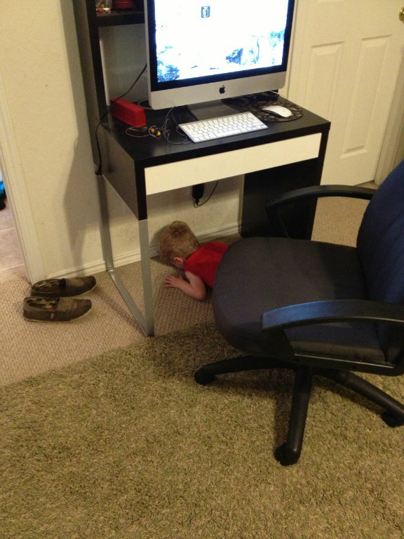 child face planting under desk
