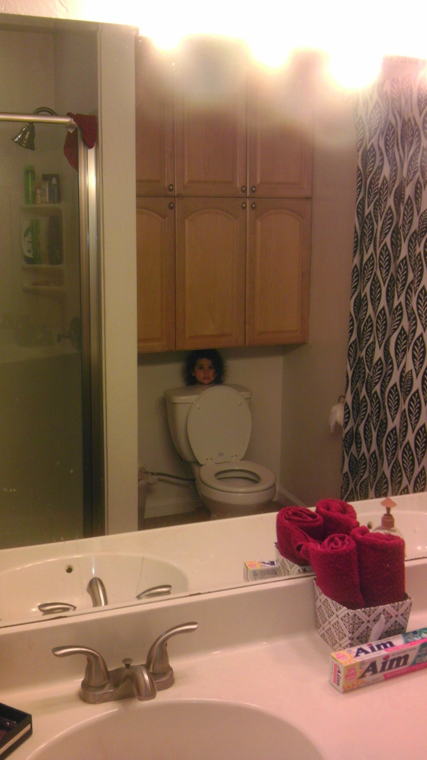 Little girl hiding behind a toilet