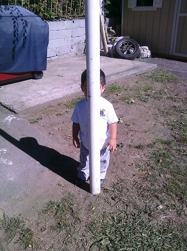 small boy hiding behind a white pole