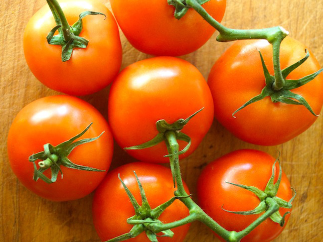 red-tomatoes-vines-ripe-green-stems-cutting-board