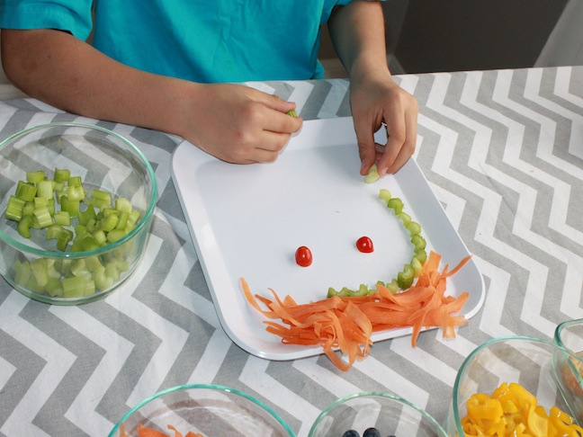 Child's Hands Making a Face out of Food on a Plate