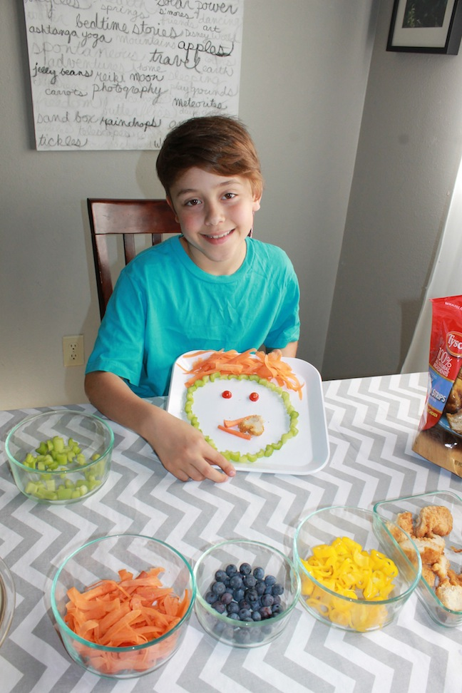 Boy showing off funny food face plate