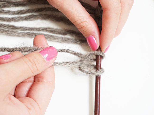 Grey yarn knotting at the top of stick