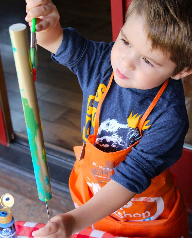 toddler-boy-painting-wood-dowel-diy-art-project-orange-apron