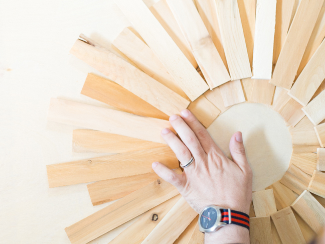 hand-pressing-wood-shims-into-wreath