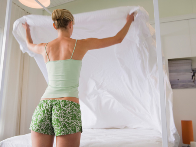 woman-making-bed-blond-shorts-white-sheets