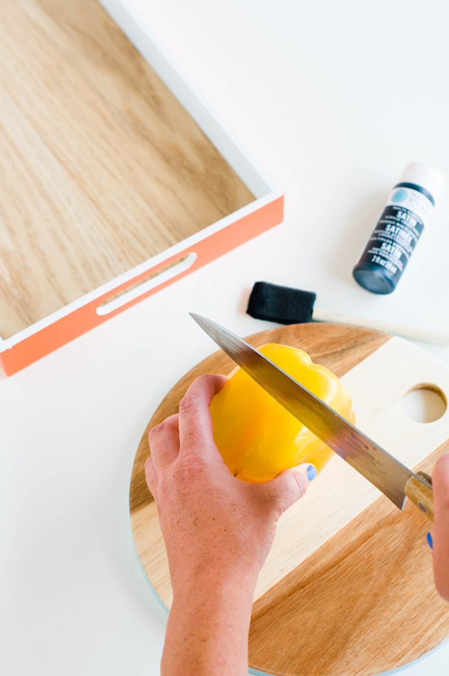 cutting yellow bell pepper wood cutting board