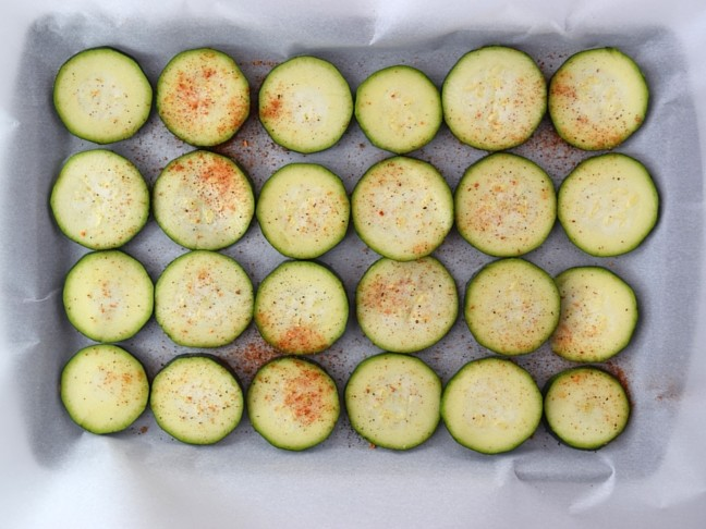 zucchini slices on parchment paper with seasoning