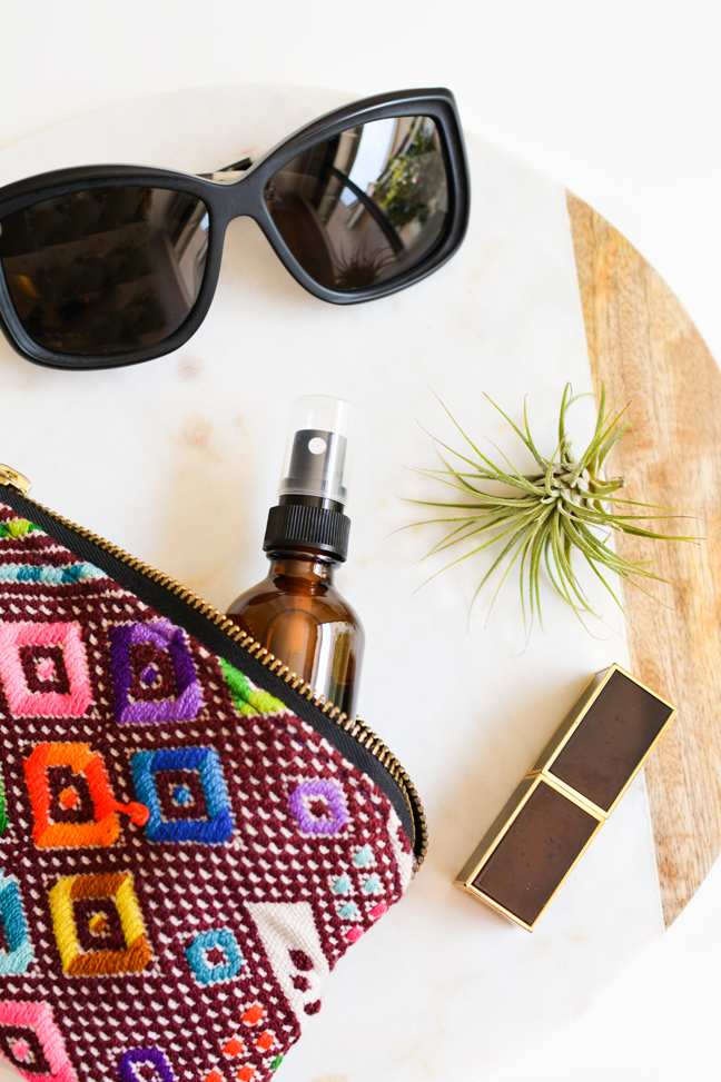 colorful makeup pouch with face mist, sunglasses, lipstick, and air plant