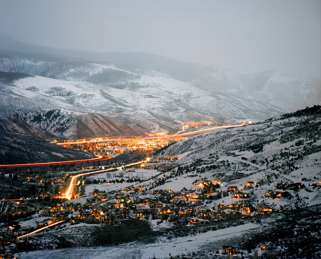 Pictured is a wide shot of Eagle Valley, located near Vail, Colorado. The town in the valley is lit up as the night approaches. It is surrounded by snow-covered hills.
