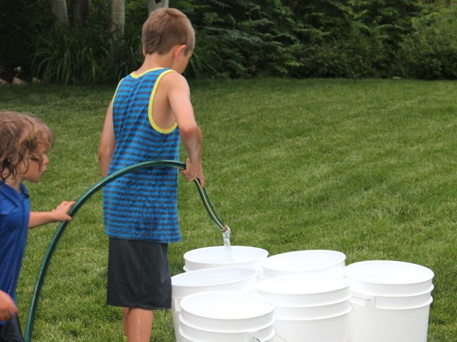 bucket-ball-outdoor-game-grass-water-hose-boy