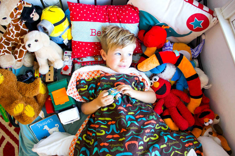little boy in bed with all of his toys