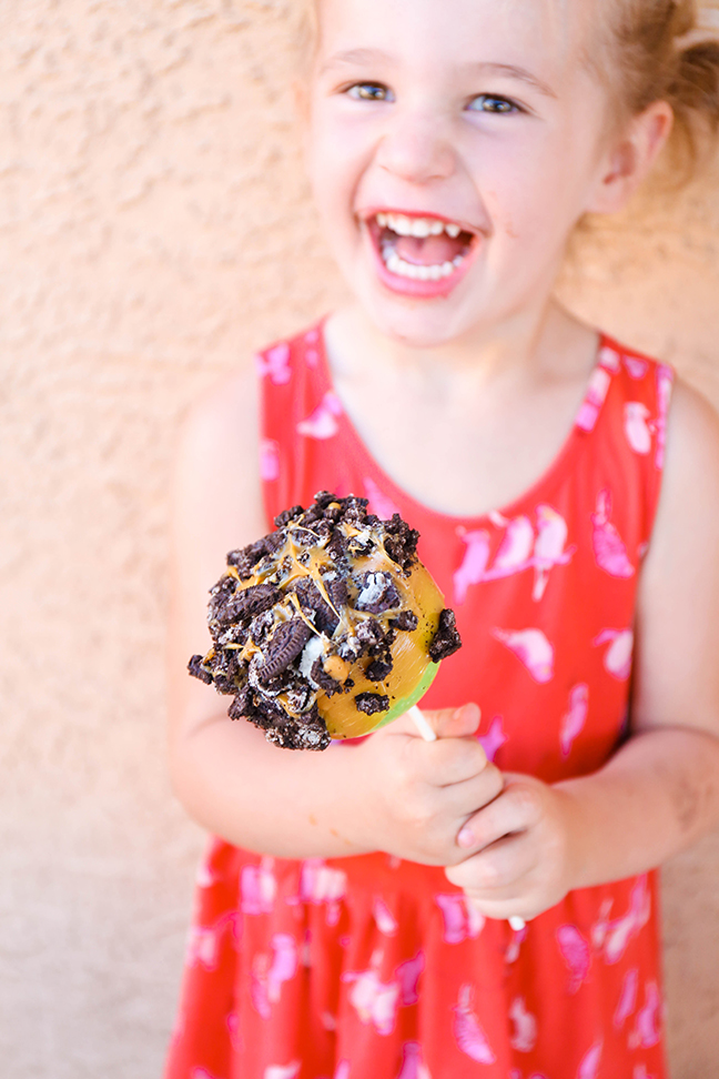 little girl holding an oreo cookie caramel apple