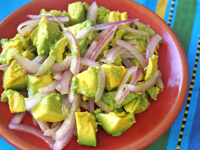 avocado-green-red plate-red onion slices-blue cloth