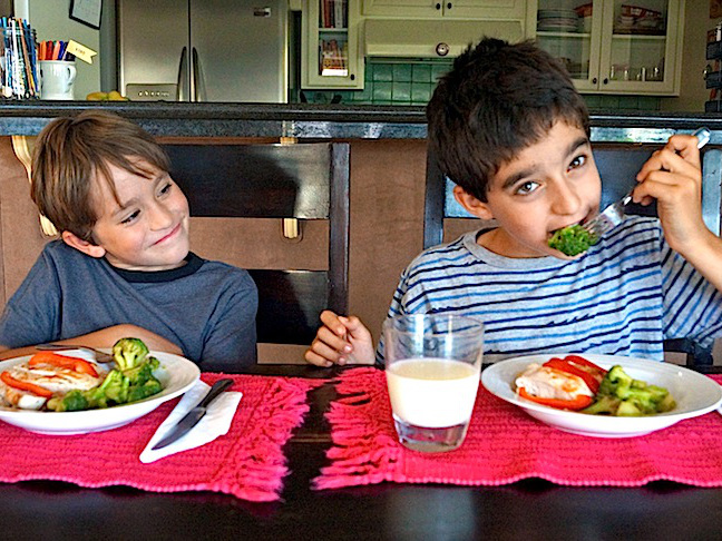 two smiling boys eating broccoli-red placemats