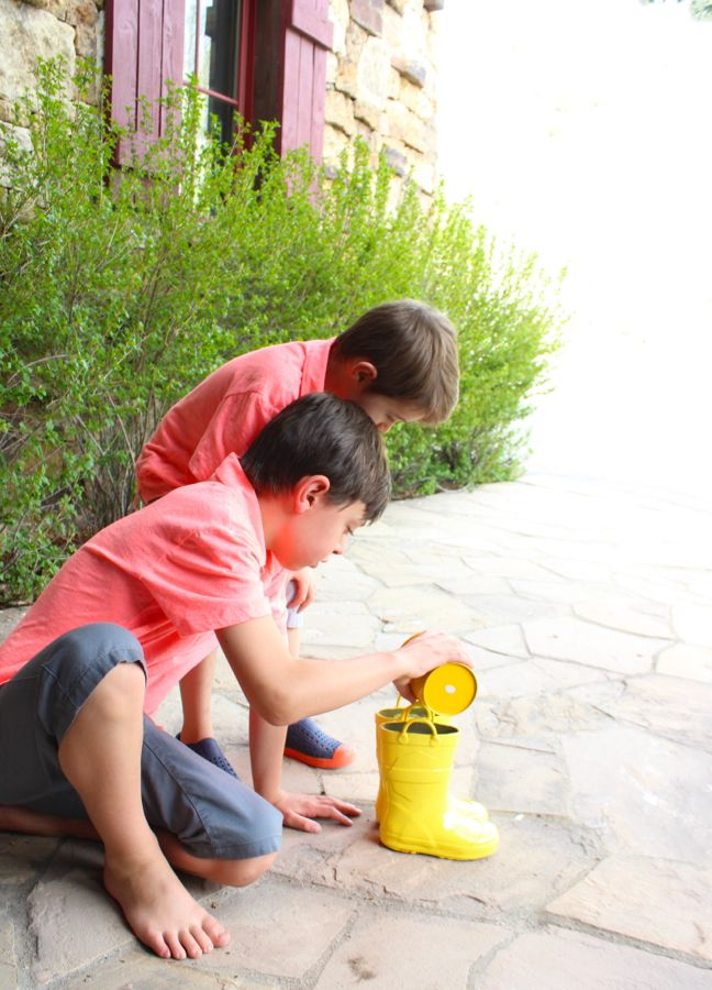 boys-filling-yellow-rain-boots-with-pebbles
