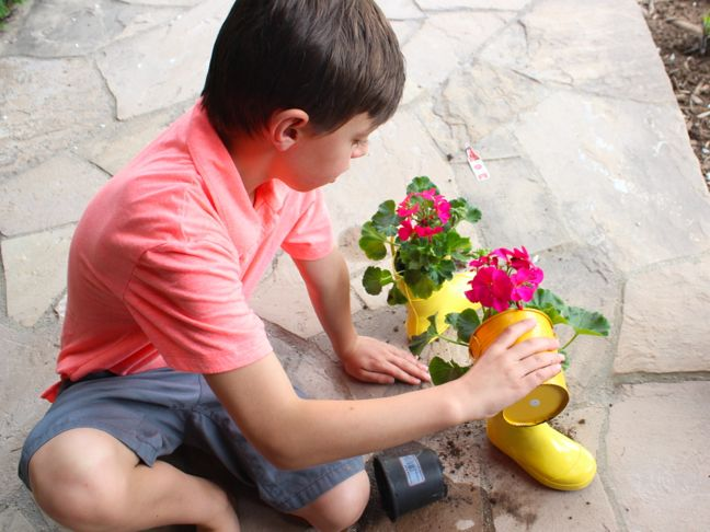 boy-planting-a-plant-inside-yellow-rain-boots