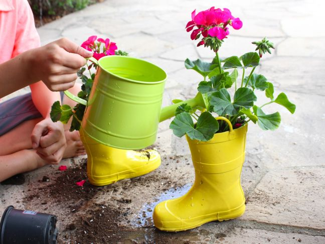 green-watering-can-watering-a-flower-inside-yellow-diy-rain-boot-planter