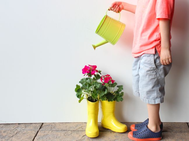 boy-watering-a-plant-inside-diy-yellow-rain-boot-planter