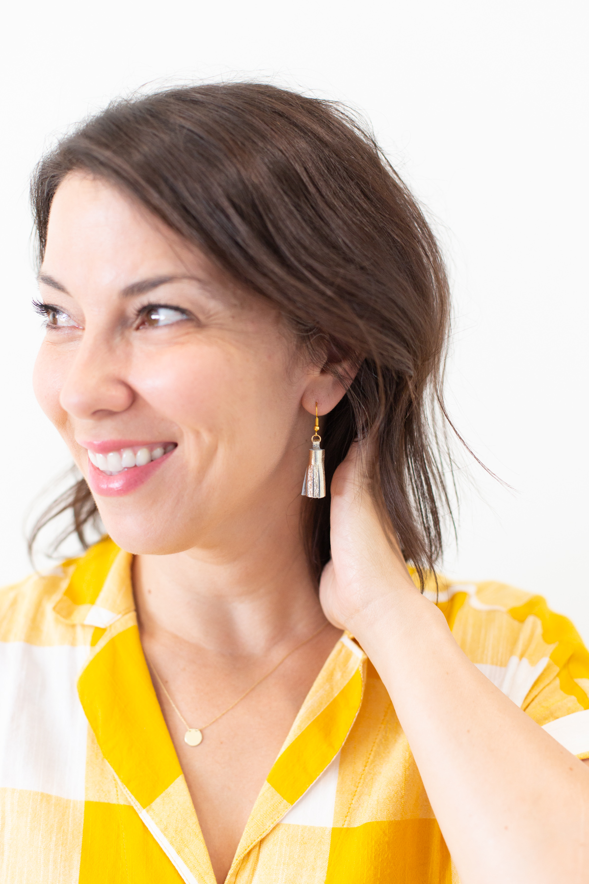 Woman wearing DIY gold tassel earrings