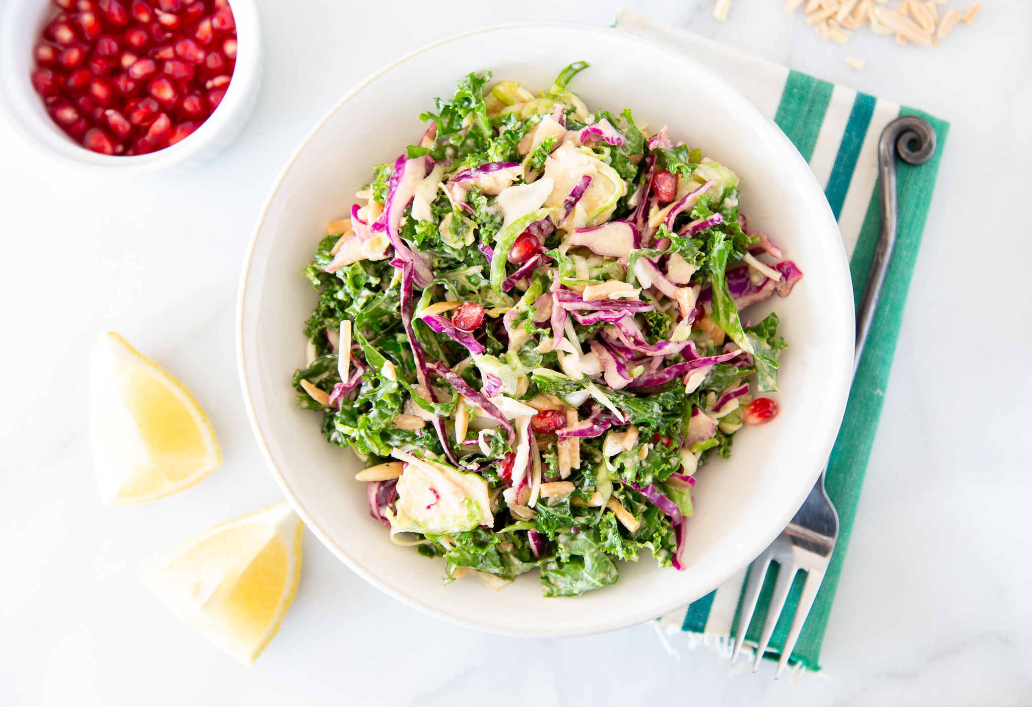 A Festive Kale and Brussels Sprouts Salad With Almonds & Pomegranate Seeds